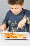Child dinner. Portrait of a boy eating dinner battered fish and chips Stock Image