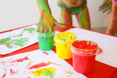 Child dipping fingers in non-toxic finger paints Stock Photo