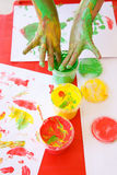 Child dipping fingers in non-toxic finger paints Royalty Free Stock Images