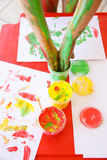 Child dipping fingers in washable finger paints Stock Images
