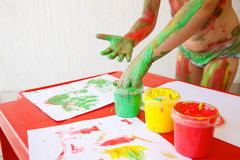 Child dipping fingers in washable finger paints Royalty Free Stock Image