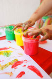 Child dipping fingers in washable finger paints Royalty Free Stock Photo