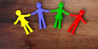 Colorful human figures holding hands laying on wooden background. 3d illustration. Child disability, autism concept. Four colorful human figures holding hands Royalty Free Stock Image