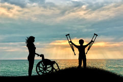 Child disabled with crutches beside wheelchair and nurse on beach. On hill. Concept help royalty free stock images