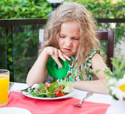 Child with disgust looking at salad Royalty Free Stock Photos