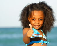 Child Displaying Thumbs Up. Young child at the beach showing a thumb up Stock Image