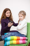 Child with displeasure giving smartphone mother. Caucasian child with displeasure giving smartphone mother Royalty Free Stock Photo