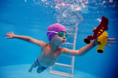 Child dives into the pool for a toy Stock Photos