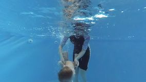 The child dives under the water in the pool. A child swims underwater in the pool with a swimming instructor stock video footage