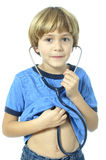 Child doctor. Young child hoping to grow up to be a doctor listens to his heart with stethoscope on white background Royalty Free Stock Photography
