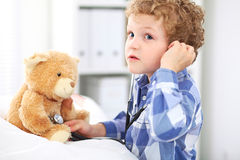 Child Doctor Checking a Teddy Bear's Heartbeat. Royalty Free Stock Image