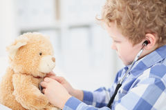 Child Doctor Checking a Teddy Bear's Heartbeat. Royalty Free Stock Images