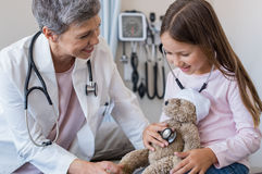 Child at doctor office. Happy little girl checking heartbeat of teddy bear in hospital. Happy pediatrician and child patient playing with stuff toy. Little girl Royalty Free Stock Images