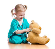Child doctor playing with plush toy Royalty Free Stock Image