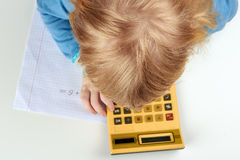 Child does  calculations with retro calculator Royalty Free Stock Images