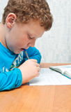 Child does homework and gnaws pen. Boy doing homework on mathematics in the room Royalty Free Stock Images