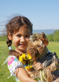 Child and dog. Smiling little girl hugging a yorkshire terrier dog in an outdoor setting Royalty Free Stock Photography