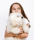 Child  and dog. Little girl with a maltese dog looking to a direction Royalty Free Stock Photography