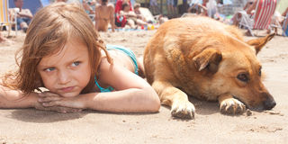 Child with dog. Little girl and her dog relaxing on the beach Royalty Free Stock Images