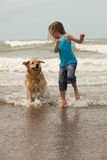 Child with dog. Little girl playing with her dog in the ocean Stock Photography