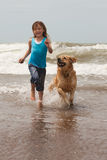 Child with dog. Pretty girl playing with her dog in the ocean Stock Photo