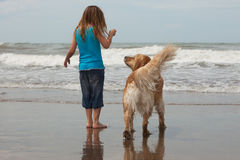 Child with dog. Little girl with her dog by the ocean Royalty Free Stock Photos