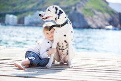 Child with dog. Happy babygirl with her dog on berth in summer Royalty Free Stock Images