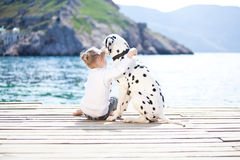 Child with dog. Happy babygirl with her dog on berth in summer Stock Image