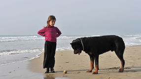 Child and dog on the beach. Little girl playing with her rottweiler on the beach Stock Image