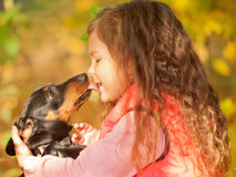 Child and dog embracing and kissing. Stock Photo