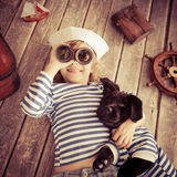 Child and dog. Happy kid dressed in sailor. Child playing with dog at home. Travel and adventure concept Stock Photography
