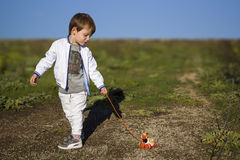 Child with the dog on a leash. Child with the toy dog on a leash Stock Photography