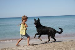 Child with dog outdoors on beach Stock Photo