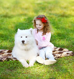 Child and dog resting on the grass. In warm sunny day royalty free stock image