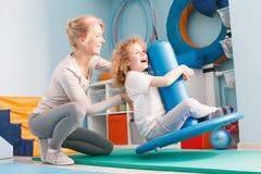 Child doing balance exercises. On therapeutic swing stock photos