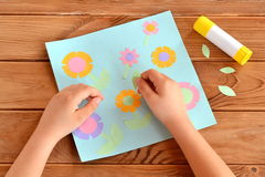 Child doing a card with flowers. Child holds a paper leaf in his hands and sticks it. Glue, greeting card on a wooden table Royalty Free Stock Photo