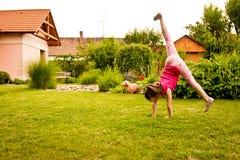 Child doing cartwheel in backyard Royalty Free Stock Photos