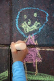 Child doing chalk drawing. A child drawing with chalk on patio pavers royalty free stock photography