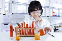 Child doing chemical research in lab. Little girl wearing coat and glasses while doing chemical research in the laboratory Royalty Free Stock Image