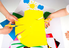 Child doing cutouts. View on hands Royalty Free Stock Photo
