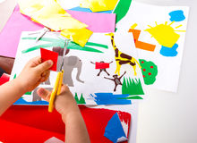 Child doing cutouts. View on hands Royalty Free Stock Image