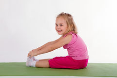 Child is doing exercise exercises on the rug stock photos
