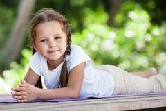 Child doing exercise on platform outdoors. Healthy lifestyle. Yoga girl Royalty Free Stock Photos