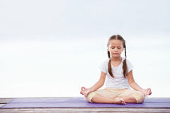 Child doing exercise on platform outdoors. Healthy lifestyle. Yoga girl Royalty Free Stock Photo