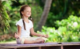Child doing exercise on platform outdoors. Healthy lifestyle. Yoga girl Stock Photo