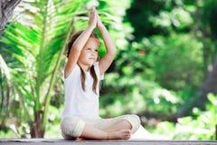 Child doing exercise on platform outdoors. Healthy lifestyle. Yoga girl Stock Photos