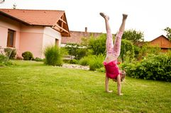 Child doing handstand in backyard Stock Photos