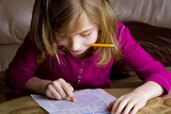 Child doing homework. A young girl studying her homework with a pencil in her mouth Royalty Free Stock Photography