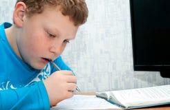 Child doing homework. Boy doing homework on mathematics in the room Stock Photo