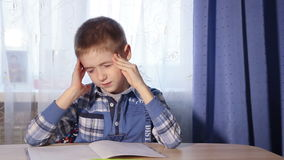 Child doing homework headache, fatigue boy to do. Child doing homework headache, f atigue boy to do the work in motion video stock footage